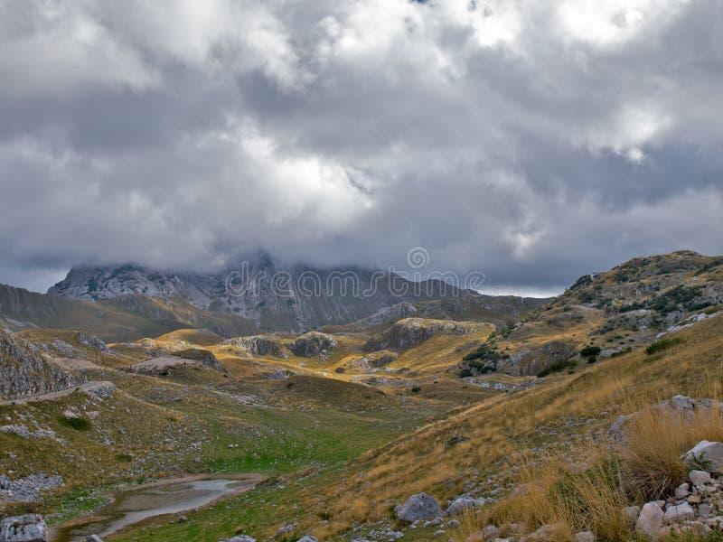 Picco di montagna nascosto dalle nubi di nimbus basse. immagine stock