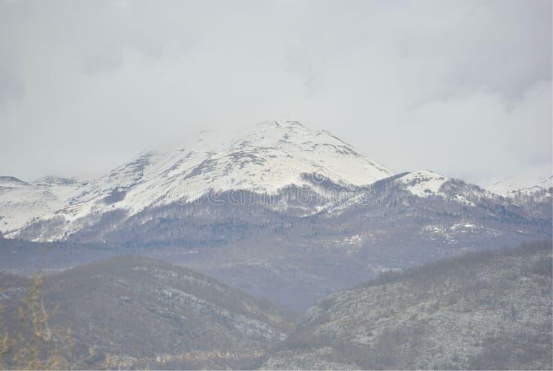 Picco di montagna in nuvola della neve fotografia stock