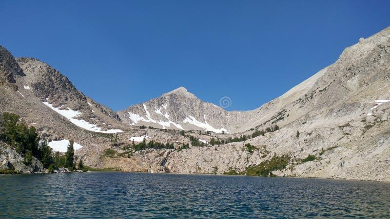 Picco di montagna sola sopra un lago fotografia stock