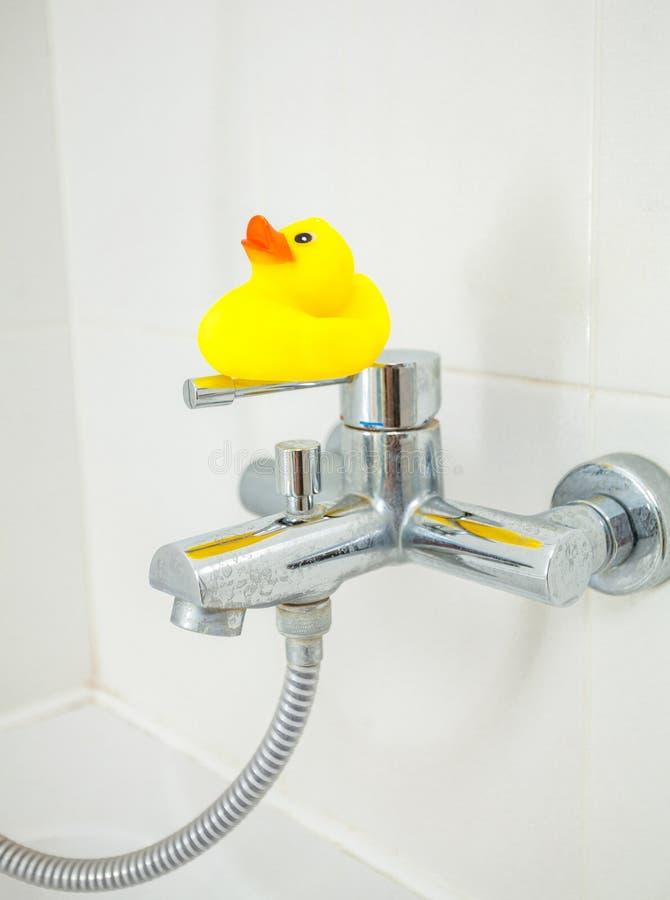 Piccola anatra di gomma che sta sul rubinetto della doccia fotografia stock libera da diritti