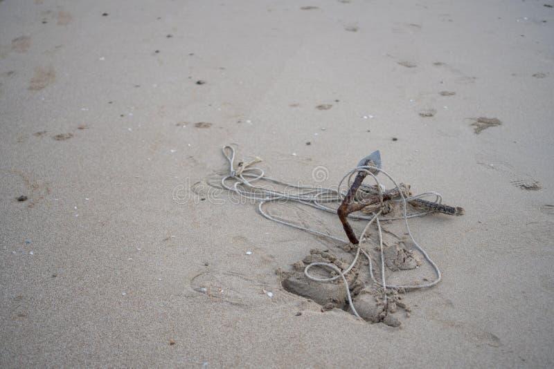 Piccola ancora arrugginita sulla spiaggia immagine stock libera da diritti