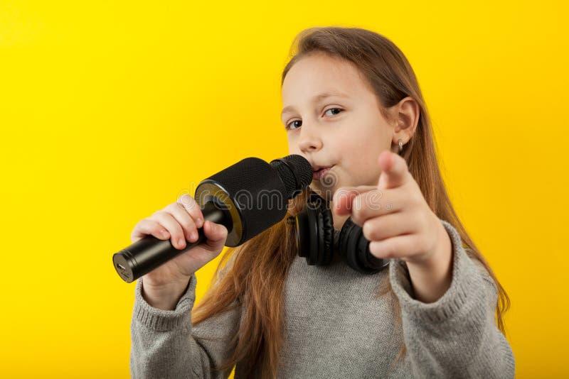 Piccola artista, talent show Canta una canzone nel microfono Ritratto su sfondo giallo fotografia stock libera da diritti