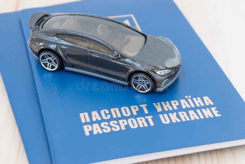 Piccola automobile del giocattolo sopra i passaporti dell'Ucraina fotografia stock