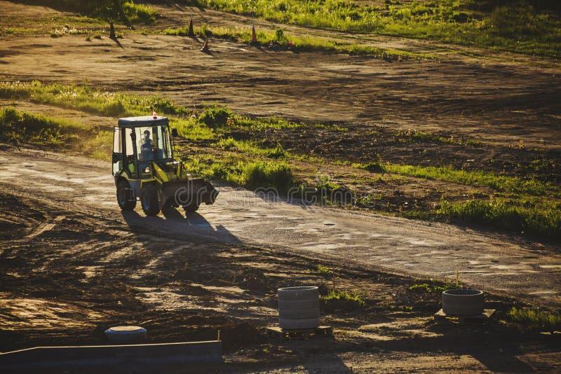 Piccola automobile dell'escavatore che passa una strada polverosa fotografie stock libere da diritti