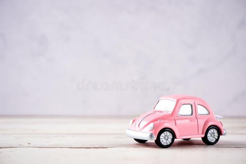 Piccola automobile di rosa dello scarabeo nel fondo in bianco per testo, concetto di giorno del ` s del biglietto di S. Valentino fotografie stock