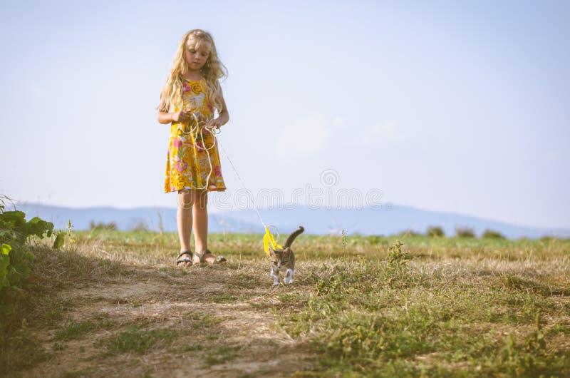 Piccola bambina che cammina con un gatto in piombo immagine stock