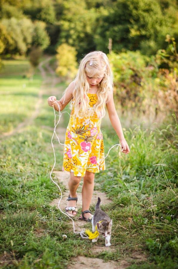 Piccola bambina che cammina con un gatto in piombo immagine stock libera da diritti