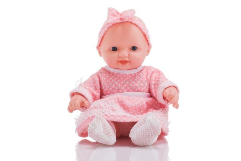 Piccola bamboletta di plastica sveglia con gli occhi azzurri che si siedono o isolata immagine stock libera da diritti