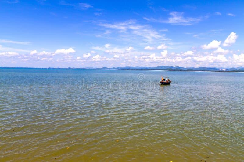 Piccola barca in baia e cielo blu alla spiaggia fotografia stock