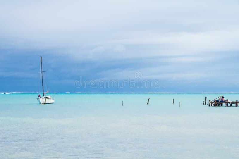 Piccola barca bianca, attraccando le poste e mar dei Caraibi nuvoloso fotografia stock