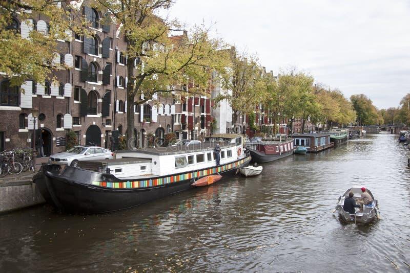 Piccola barca che passa le case galleggianti nel brouwersgracht immagini stock libere da diritti
