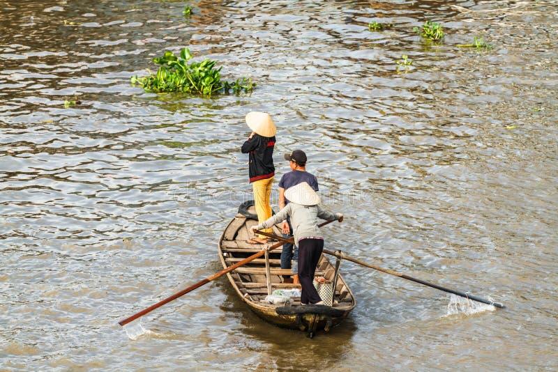Piccola barca che trasporta la gente per andare di nuovo al mercato di galleggiamento nel Mekong, Vietnam fotografia stock libera da diritti