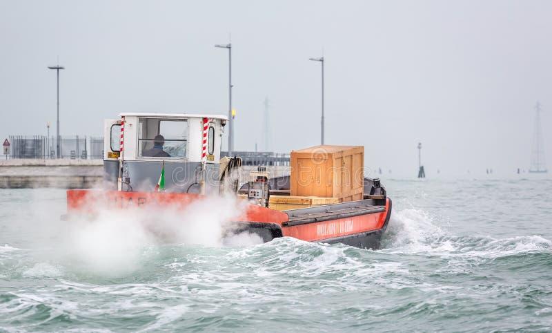 Piccola barca di trasporto di carico con la cassa di legno che ara attraverso le onde sul canale a Venezia, Italia immagine stock