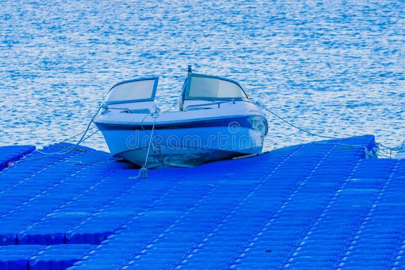 Piccola barca messa in bacino ad un pilastro blu immagini stock