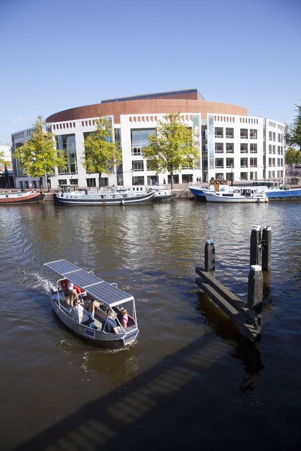 Piccola barca nel amstel del fiume davanti al teatro dell'opera immagini stock libere da diritti