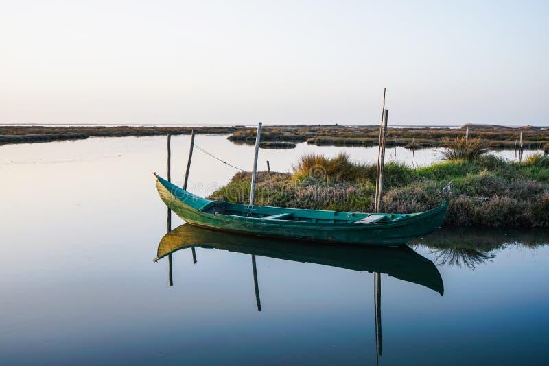 Piccola barca stagionata vicino alla riva in laguna pacifica e bella il giorno luminoso Riflessione della barca su acqua immagini stock