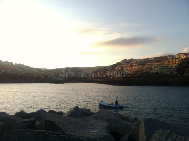 Piccola barca in una baia davanti ad una piccola città italiant immagini stock libere da diritti
