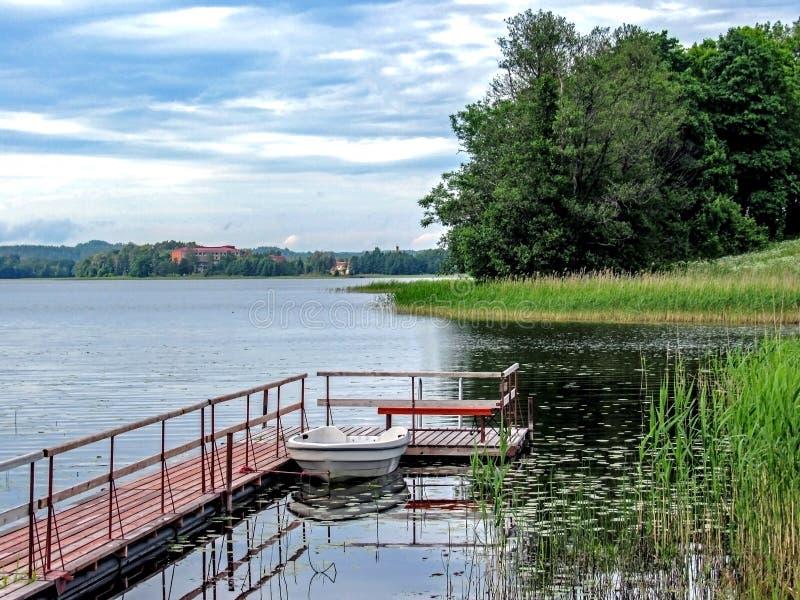 Piccola barca vicino al pilastro di legno sul lago con la foresta verde sui precedenti fotografie stock libere da diritti