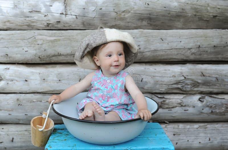 Piccola bella neonata in ciotola di lavatura dei piatti contro lo sfondo di una parete della casa di legno immagine stock