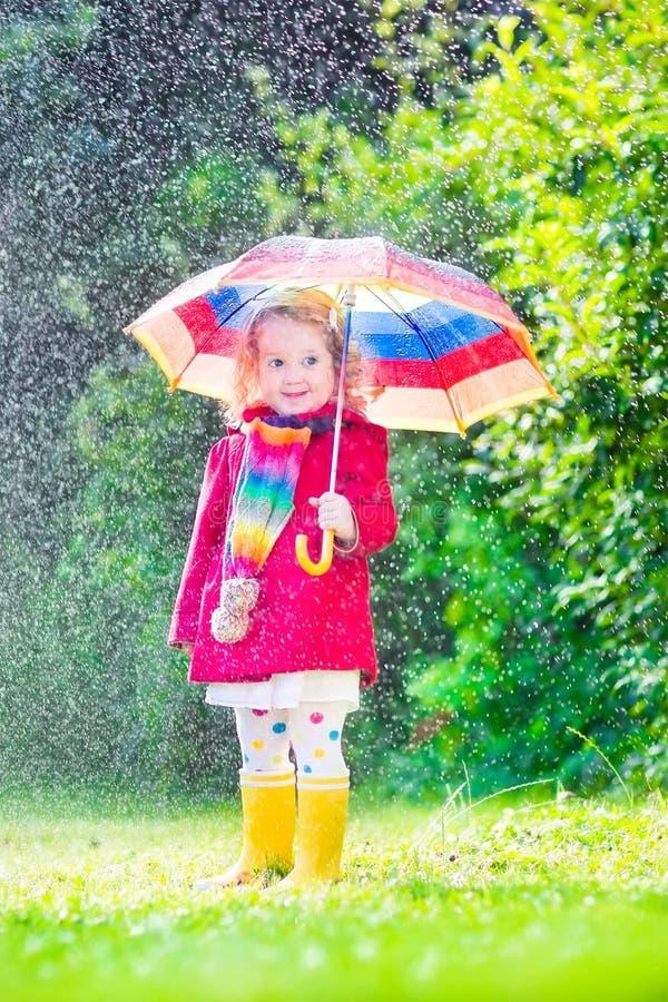 Piccola bella ragazza che gioca nella pioggia immagine stock