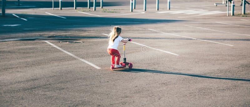 Piccola bella ragazza che guida un motorino fotografie stock libere da diritti