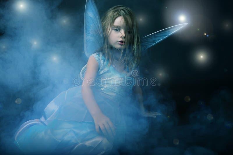 Piccola bella ragazza in vestito blu con le ali. immagini stock libere da diritti