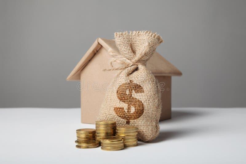 Piccola borsa con soldi ed il simbolo di dollaro Pila di monete e di modello della casa Proprietà finanziaria di ipoteca Affitto  fotografia stock libera da diritti