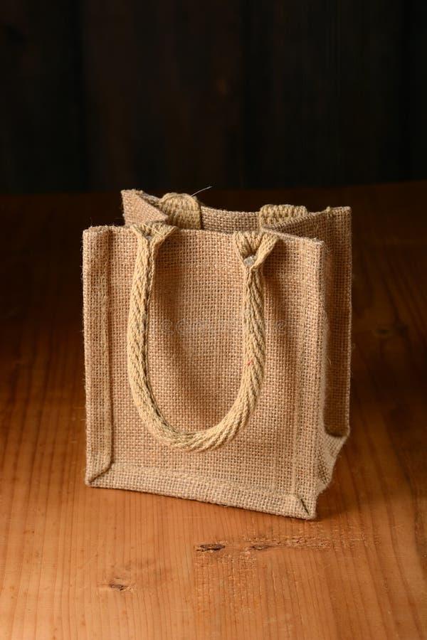 Piccola borsa della iuta sulla tavola di legno immagini stock