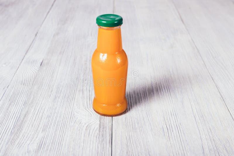 Piccola bottiglia dei supporti del succo d'arancia sulla tavola di legno bianca fotografia stock