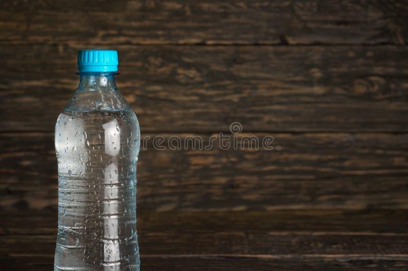 Piccola bottiglia di acqua pulita con le gocce immagini stock
