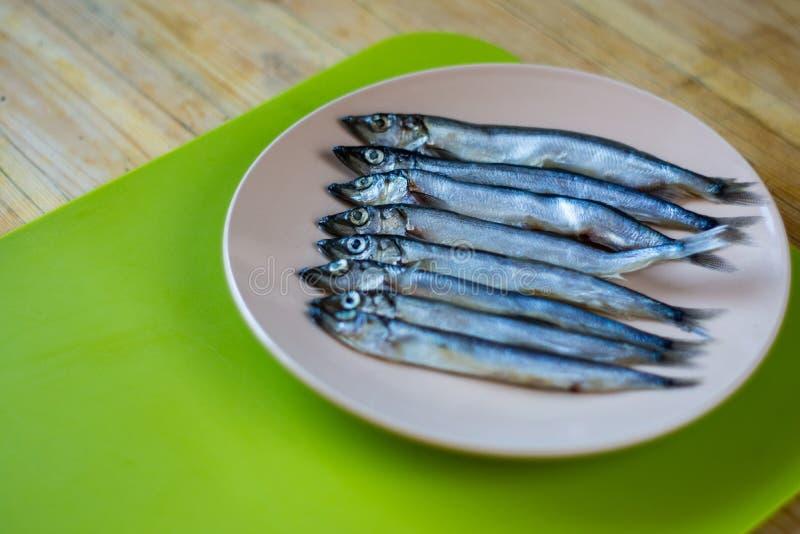 Piccola bugia del pesce d'argento in un piatto beige immagine stock