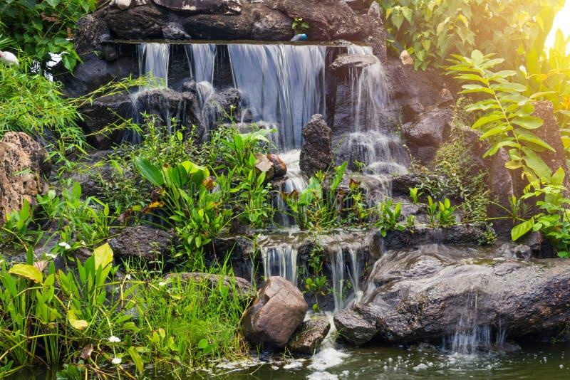 Piccola caduta artificiale dell'acqua nello spazio di verde della casa del giardino del parco fotografia stock libera da diritti