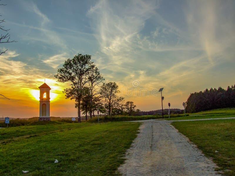 Piccola cappella che copre grande tramonto immagine stock