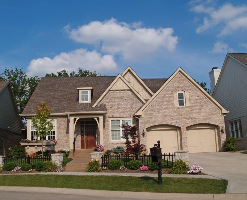 Piccola casa beige del mattone con un garage delle due automobili in Fron immagini stock