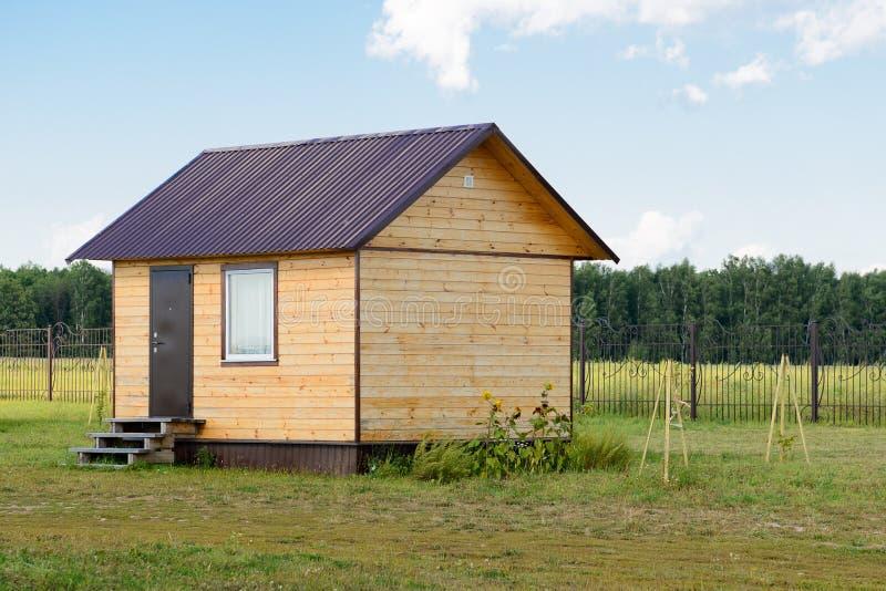 Piccola casa di pannello di legno su una zona verde fotografia stock