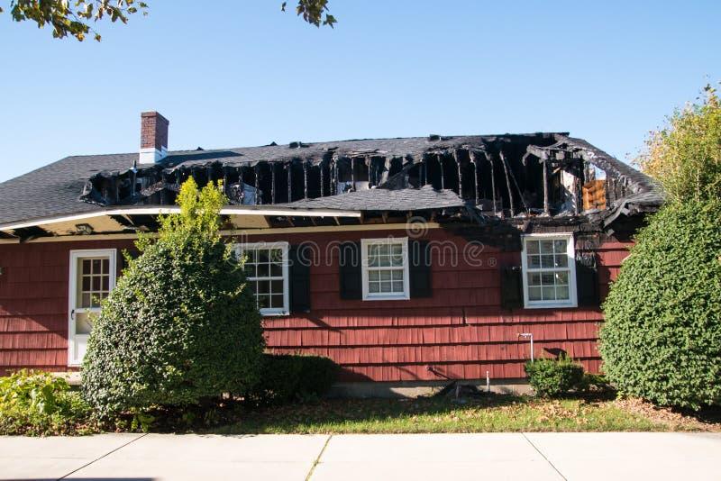 Piccola casa rossa con il tetto e l'ultimo piano distrutti da incendio fotografia stock