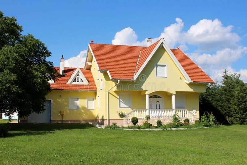 Piccola casa suburbana gialla moderna della famiglia con il garage circondato con erba verde e gli alberi fotografie stock
