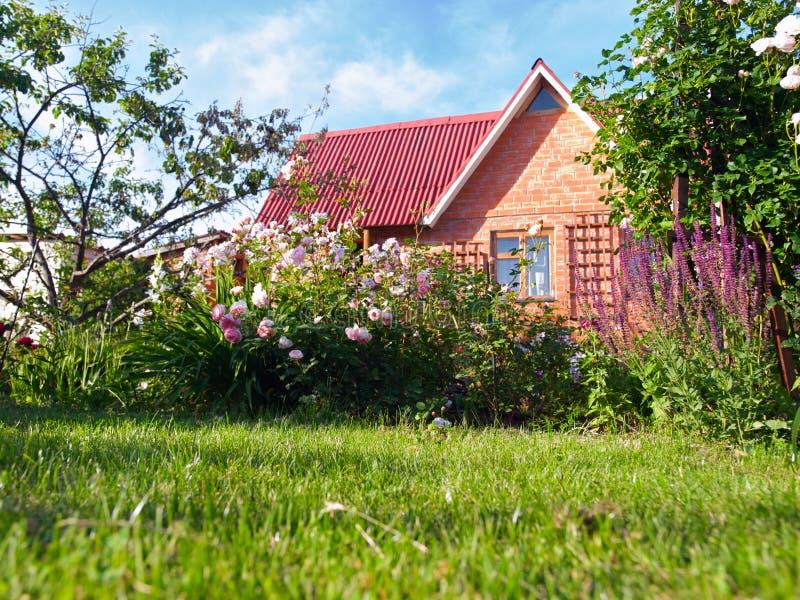 Piccola casa in un giardino di fiore fotografie stock libere da diritti