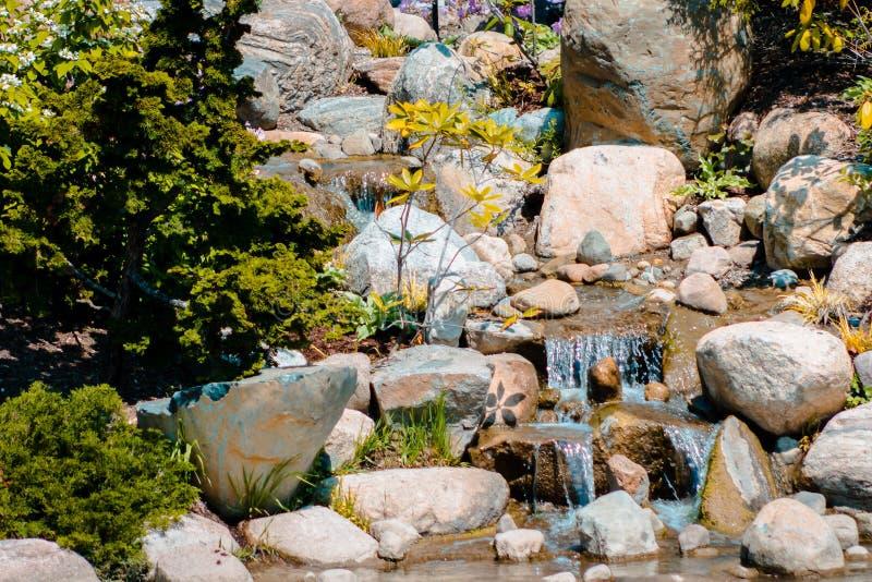 Piccola cascata che sfocia in uno stagno ai giardini giapponesi a Grand Rapids Michigan fotografie stock