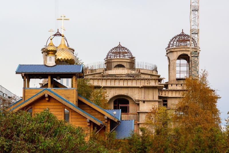 Piccola chiesa di legno con un tetto blu e cupole dorate sui precedenti di grande tempio fotografia stock libera da diritti