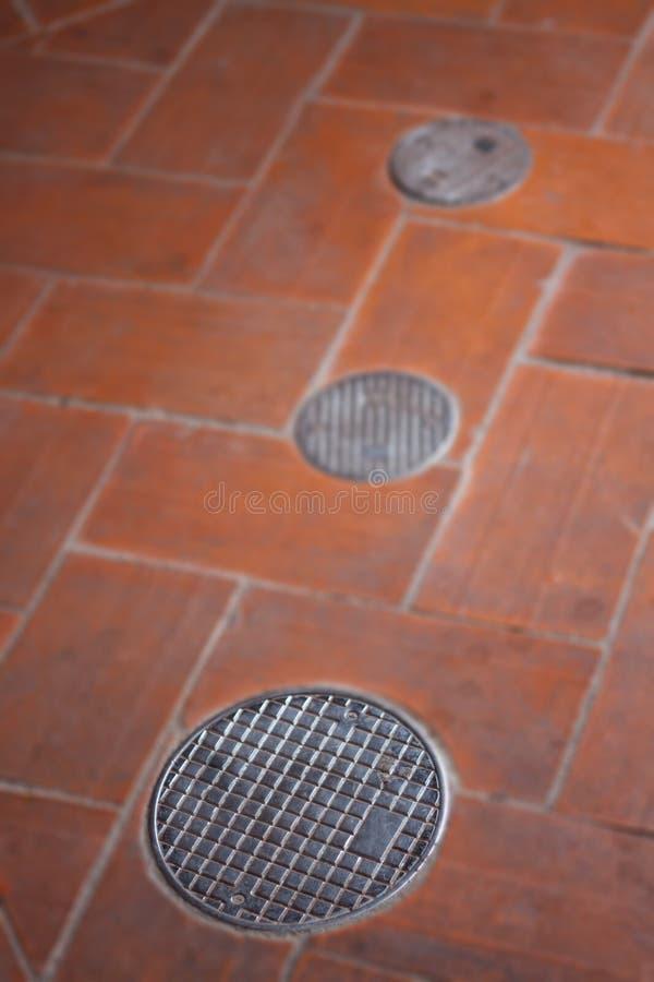 Piccola copertura di botola rotonda sul sentiero per pedoni fotografia stock