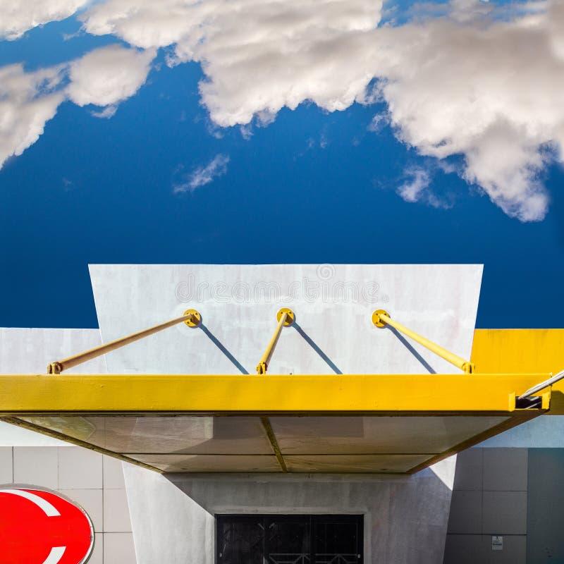 Piccola costruzione in giallo ed in rosso con un fondo del cielo blu immagine stock libera da diritti
