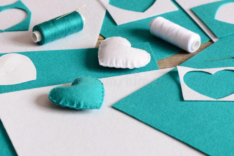 Piccola decorazione farcita dei cuori Cuori fatti di feltro, del filo, degli strati del feltro e dei residui, ago sulla tavola Di immagine stock