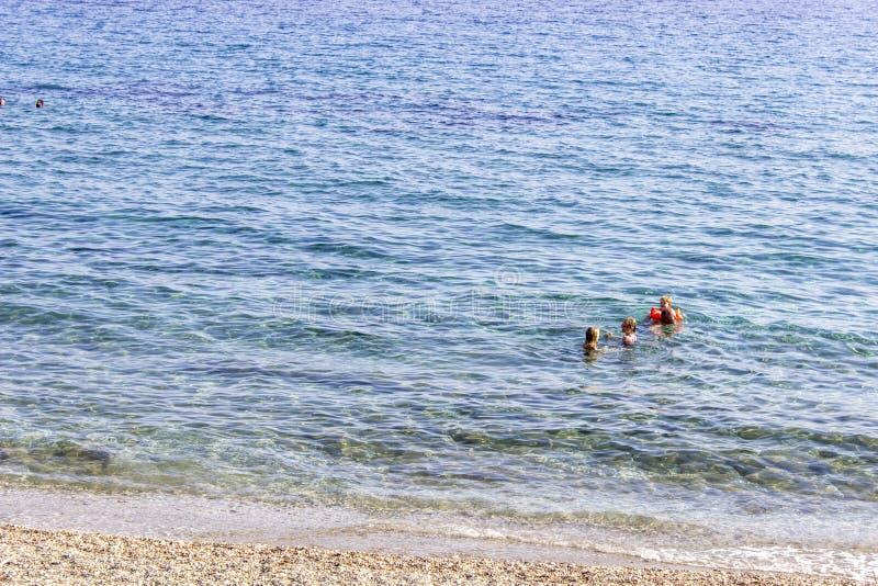 Piccola famiglia che nuota in chiaro mare blu a Plomari in Lesvos fotografia stock libera da diritti