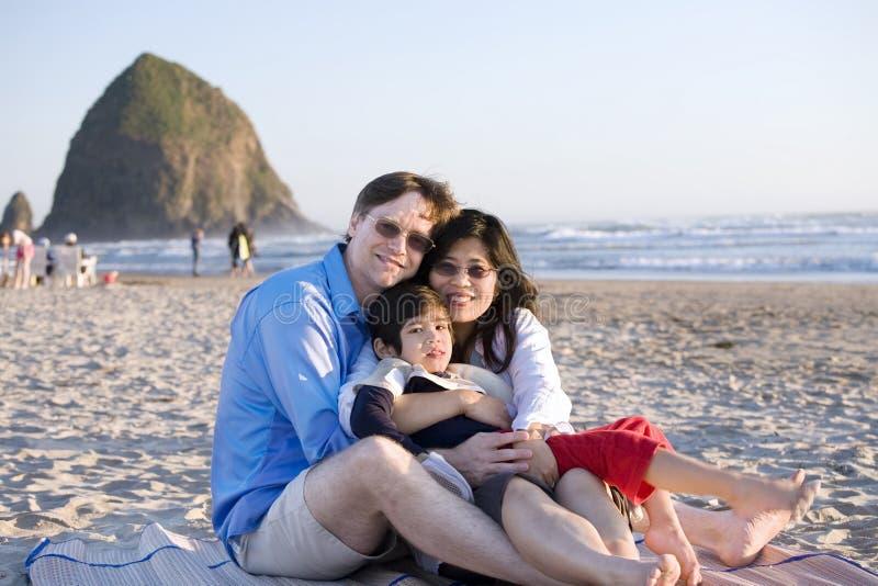 Piccola famiglia con il ragazzo invalido che si siede alla spiaggia immagine stock