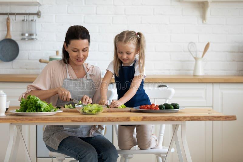 Piccola figlia che aiuta la giovane mamma orgogliosa a tagliare verdure fresche fotografia stock libera da diritti