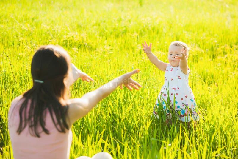 Piccola figlia che corre felicemente verso la sua mamma fotografia stock