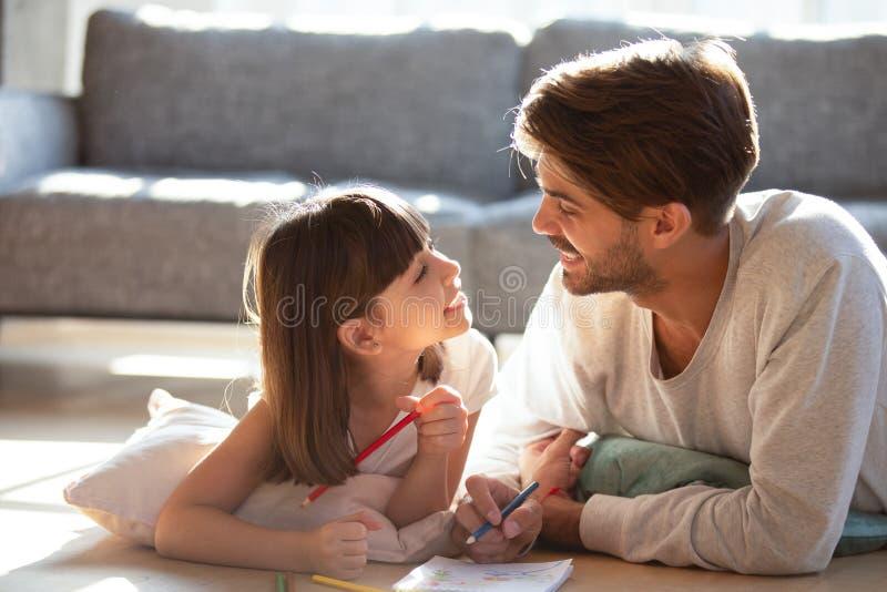 Piccola figlia del padre che si trova sul pavimento che disegna e che parla immagini stock