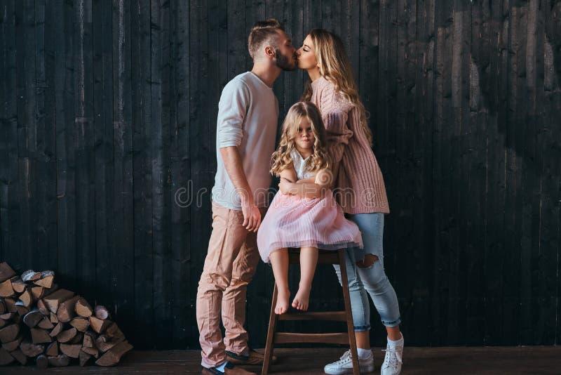 Piccola figlia turbata che si siede con i braccioli attraversati su una sedia mentre il suo bacio dei genitori nella stanza vuota fotografia stock