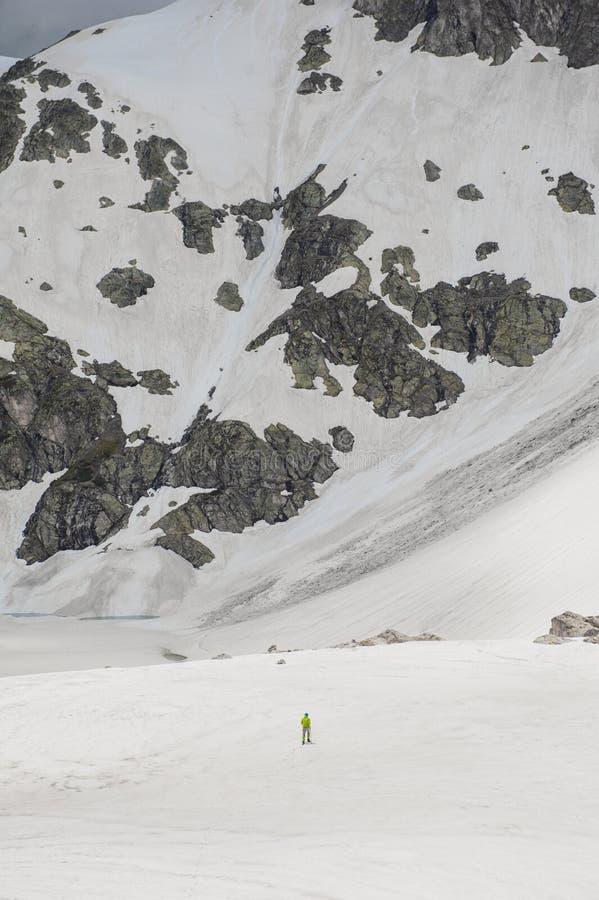 Piccola figura dell'uomo sul grande spazio della neve del ghiacciaio fotografia stock